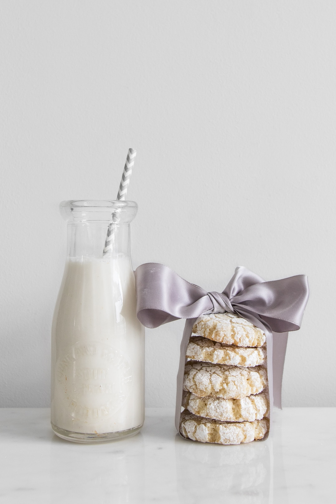 Stack of amaretti cookies wrapped in lavender ribbon next to a glass bottle of milk with a straw