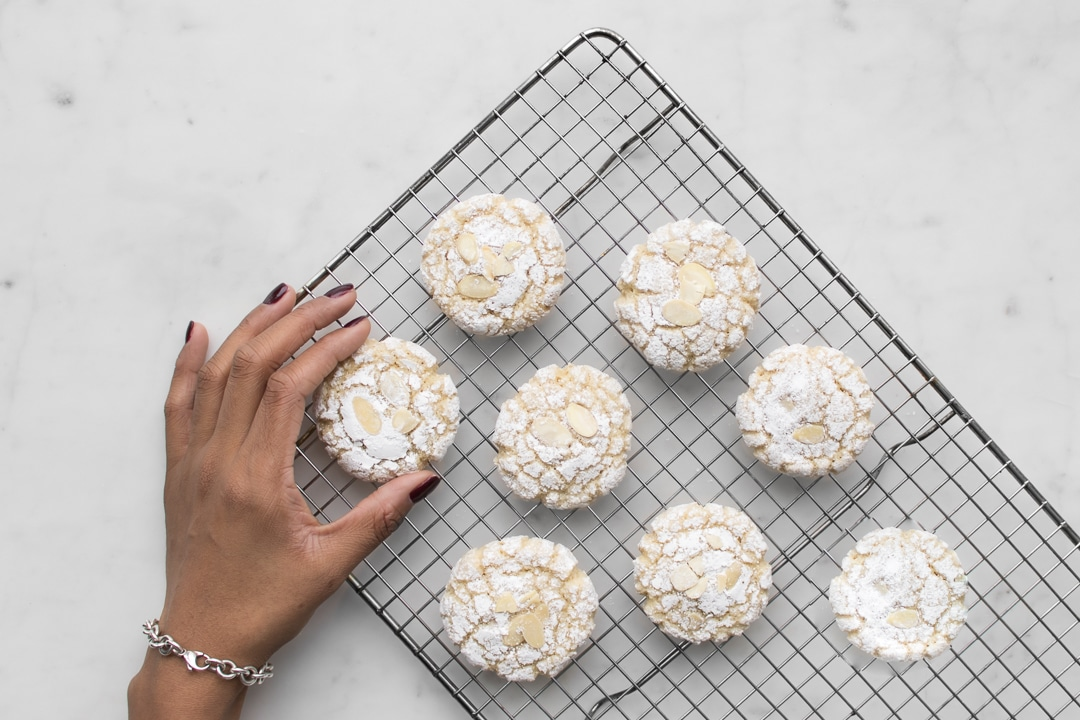 Mystique's hand grabbing an amaretti cookie from a cooling rack with eight cookies