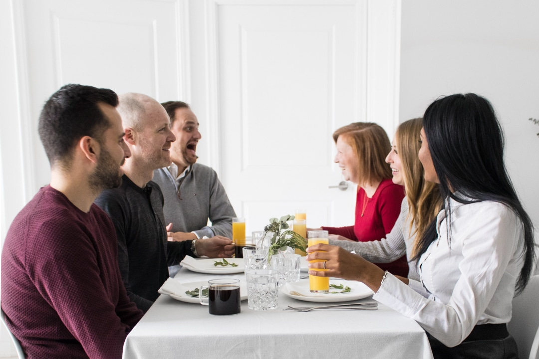 Philip and Mystique drinking mimosas at the table with their holiday brunch guests