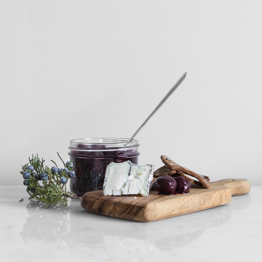 Pickled cherries on a wooden board with blue cheese and crackers