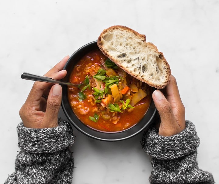 Mystique's hands holding a black bowl with Cabbage Roll Soup and a piece of bread.