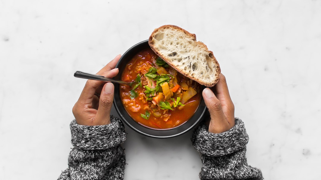 Close up photo of a person's hands holding a bowl of soup with bread on the bowl.