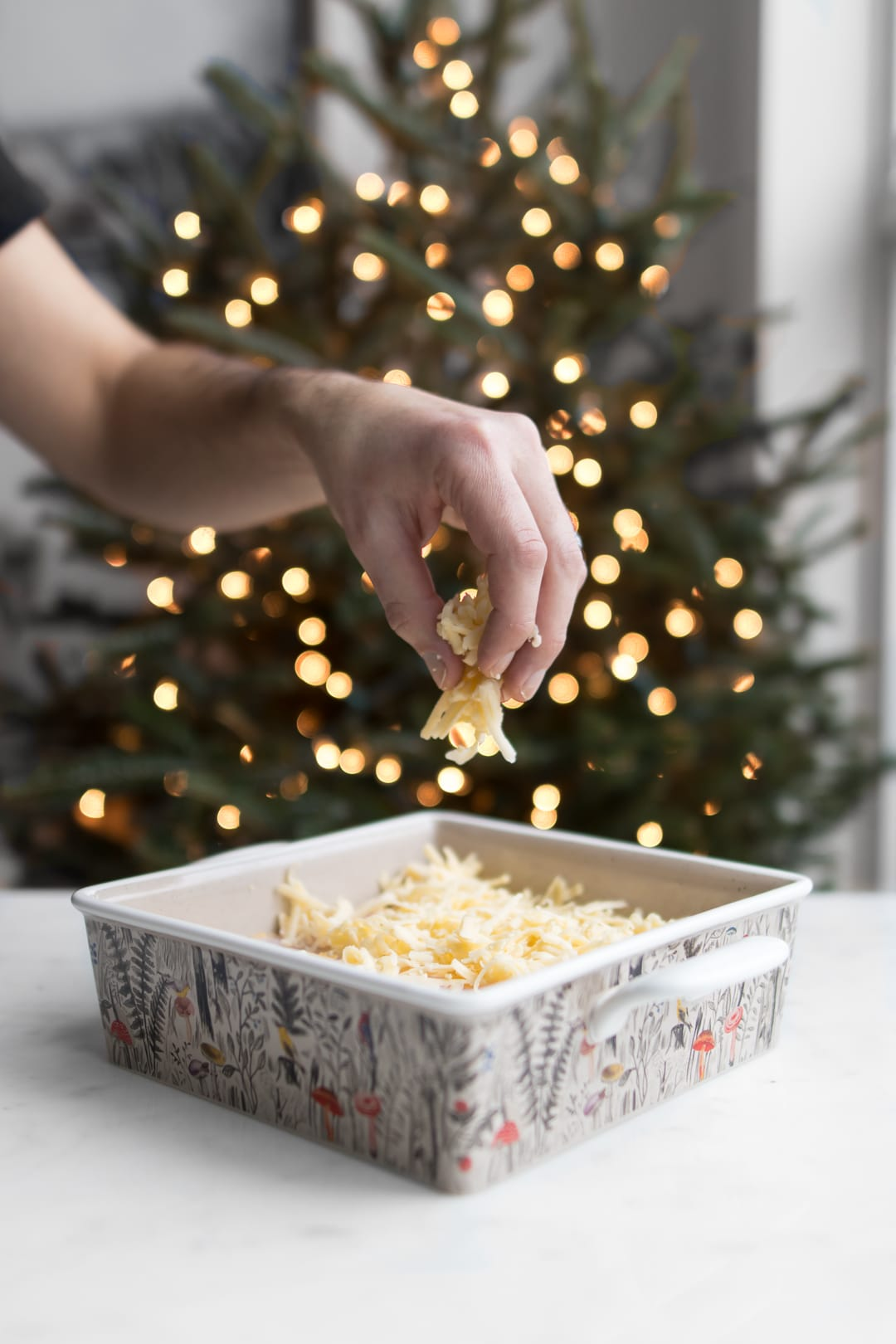 Man's hand sprinkling cheese on breakfast casserole with Christmas tree in the background