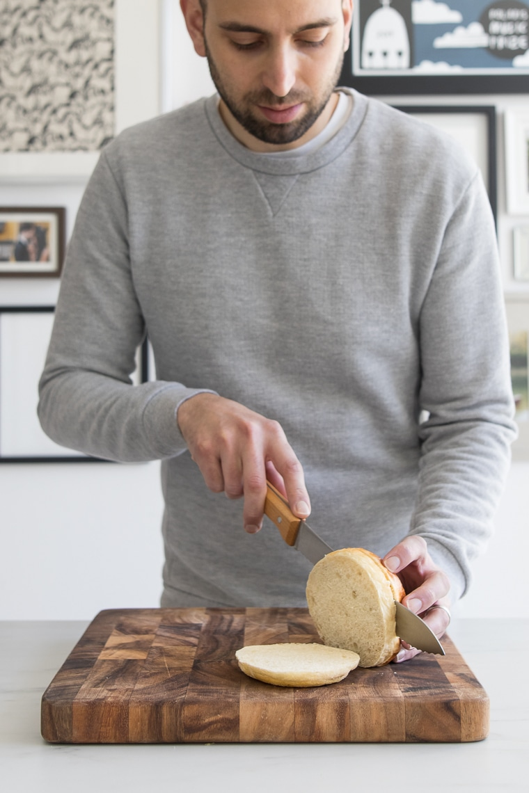 Male slicing a hamburger bun into three slices