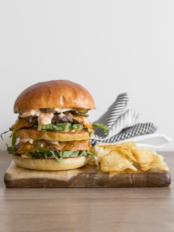 Homemade Big Mac on a wooden board with chips