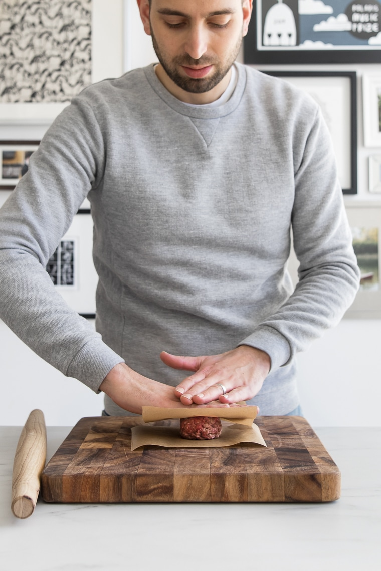 Male flattening out balls of ground beef in between two pieces of parchment paper
