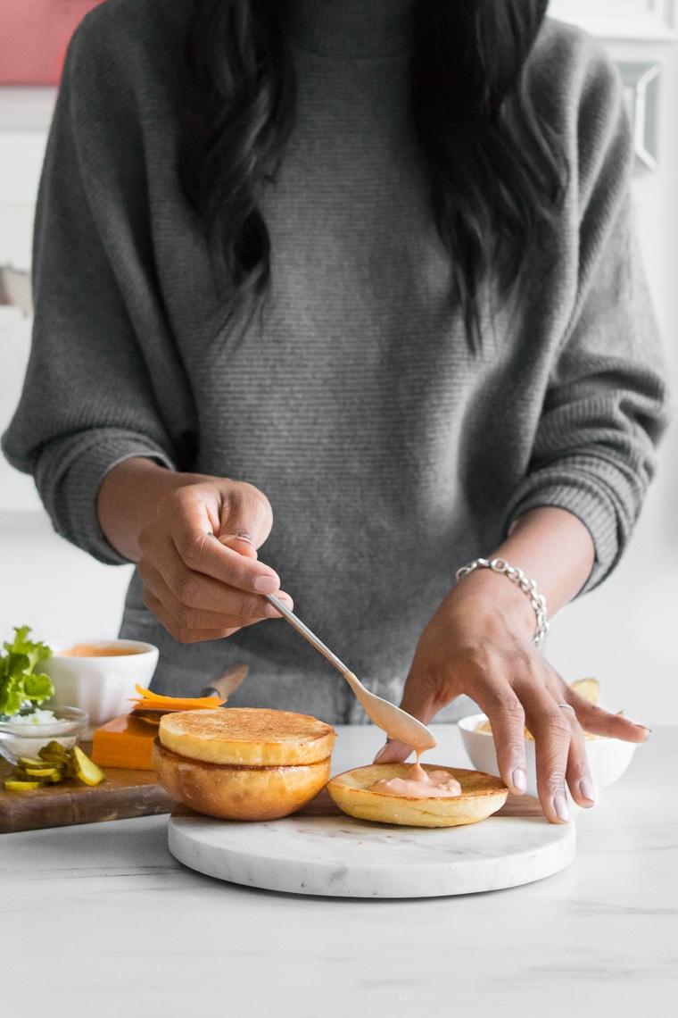 Female spooning secret sauce onto the bun