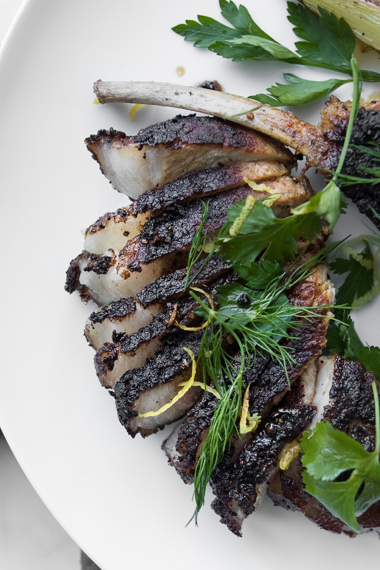 Close up of sliced fennel rubbed pork chop from the Dining In Cookbook