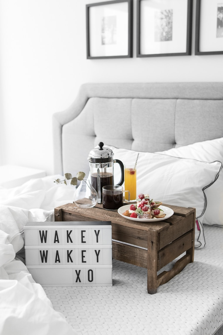 """Wakey Wakey XO"" on small cinema sign laying on an Endy mattress with a cup of coffee, french toast, a newspaper, and two Endy pillows"