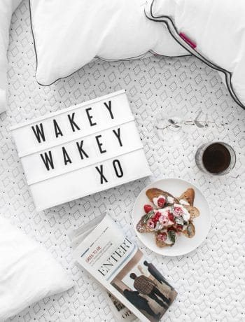 "Overhead of ""Wakey Wakey XO"" on small cinema sign laying on an Endy mattress with a cup of coffee, french toast, a newspaper, and two Endy pillows"