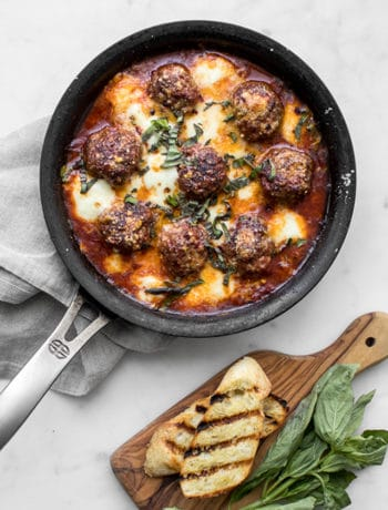 Skillet of Meatballs with cheese, tomato sauce, grilled bread and fresh basil