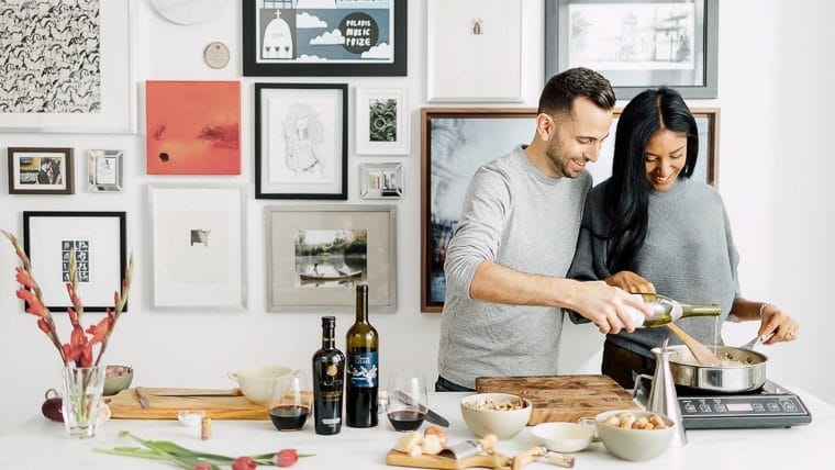 Phil pouring white wine into a pot of risotto while Mystique stirs