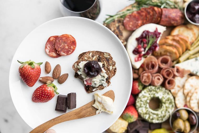 A white plate with salami, strawberries, almonds, chocolate and a cracker with blue cheese and cherry held over a cheese and charcuterie board