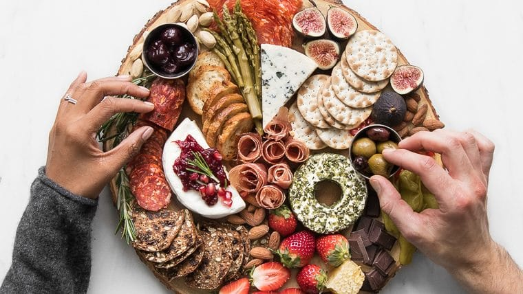 Hands grabbing food from a cheese and charcuterie board