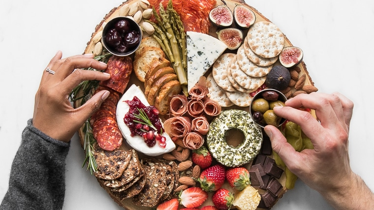 Philip and Mystique's hands grabbing food from their romantic cheeseboard