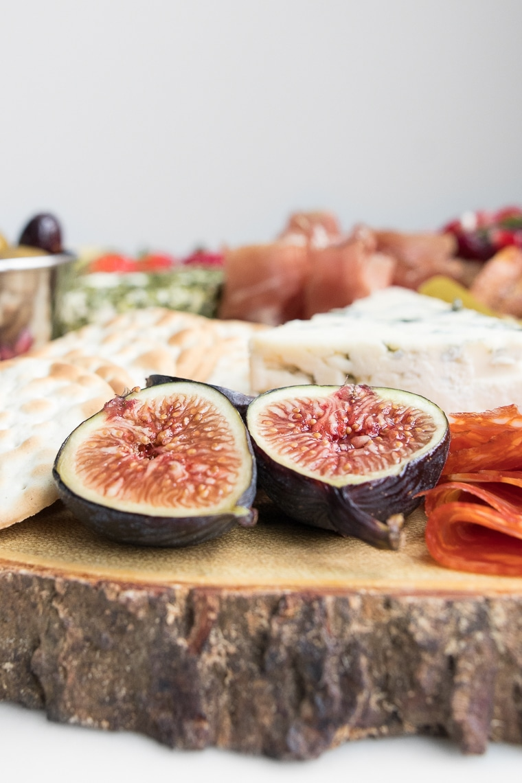 Close-up of halved fig on a wood cheeseboard