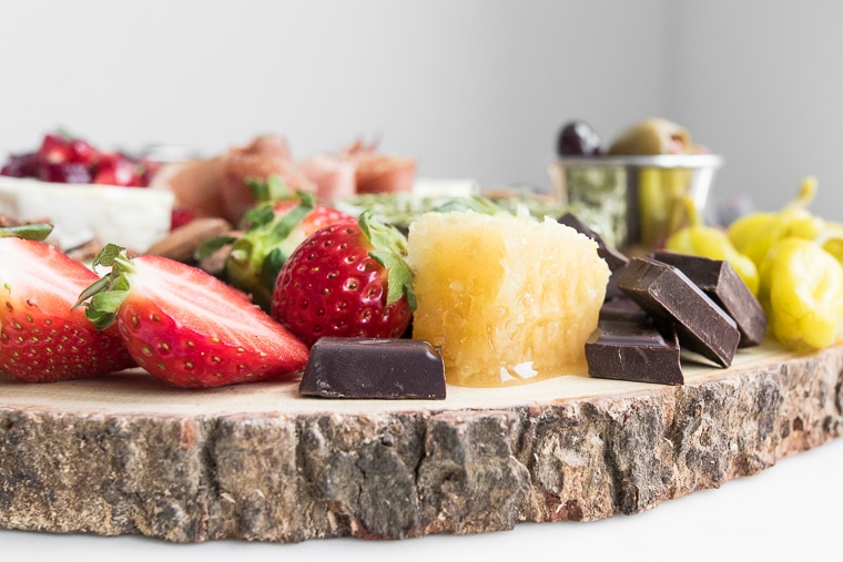 Close-up side view of cheeseboard featuring sliced strawberries, chocolate squares, honeycomb and peppers