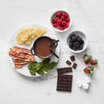 Overhead of Dark Chocolate Fondue for Two in a small cast iron pot surrounded by a chocolate bar, mint leaves, chips, strawberries, and bowls of raspberries and blackberries