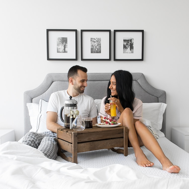 Philip and Mystique sitting on their bed looking at each and smiling while they eat French Toast. Bed has a grey headboard and 3 black and white pictures hanging above.