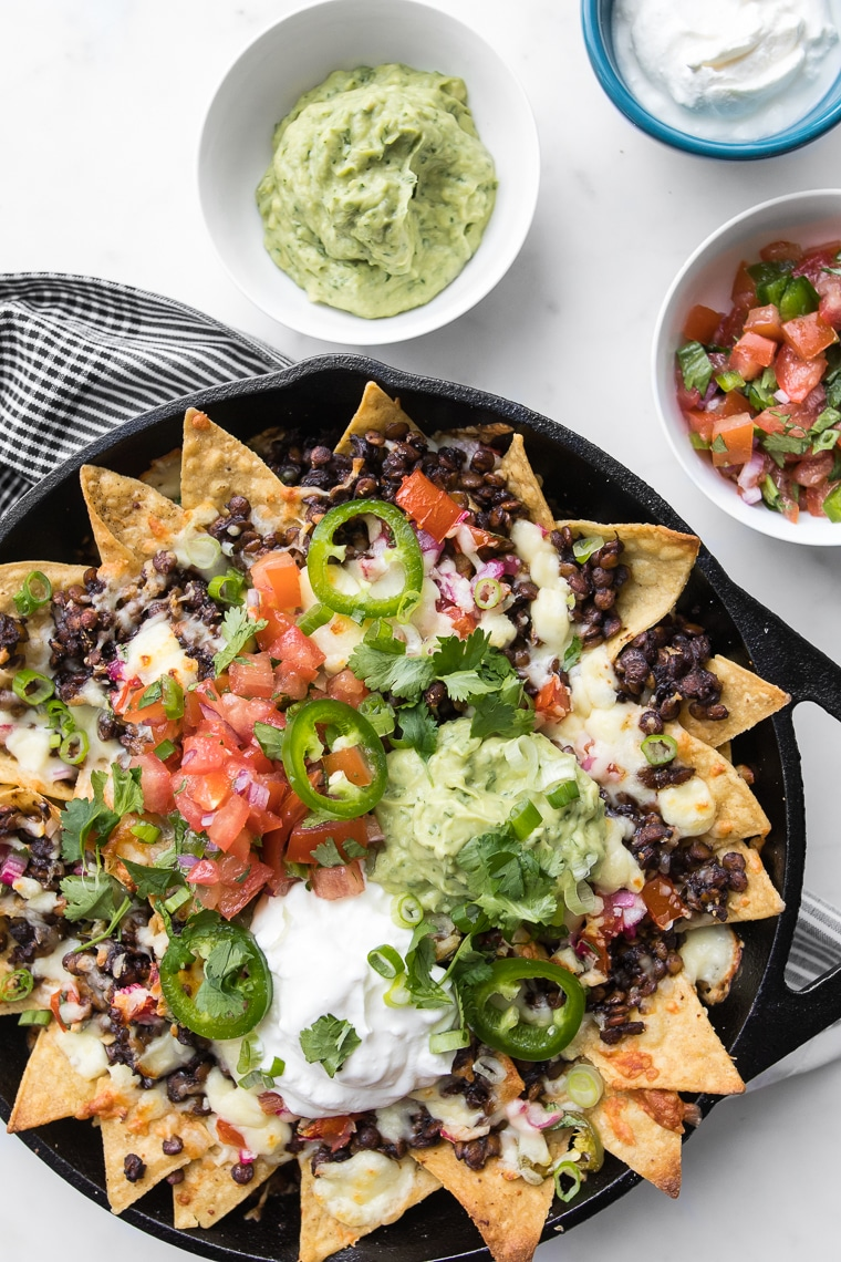 Loaded Nachos with Lentils in a Black Skillet with Guacamole, Sour Cream and Salsa