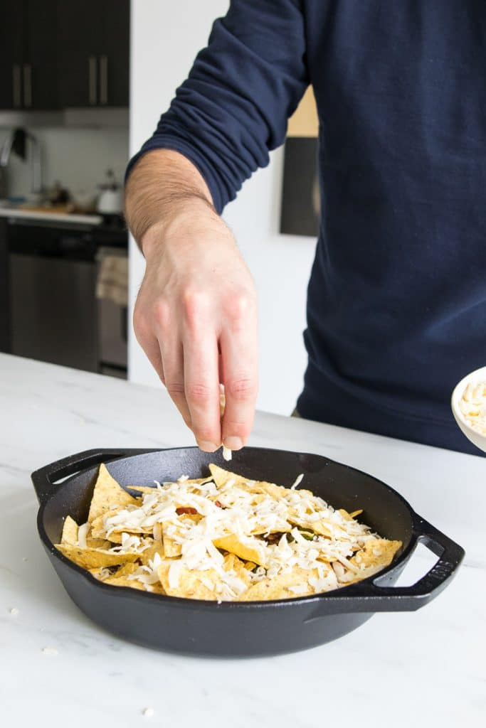 Sprinkling cheese onto nachos