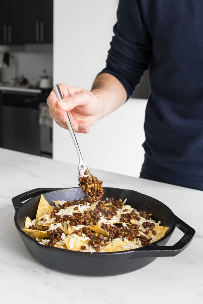 Spreading cooked lentils onto nacho chips