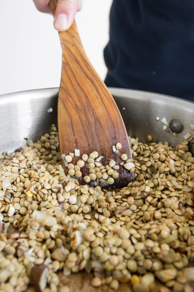 Stirring green lentils in a skillet