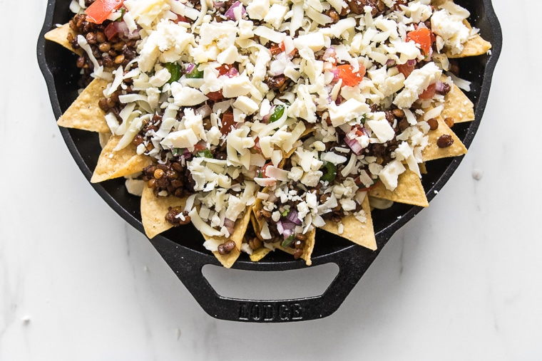 The loaded nachos smothered in white cheese prior to baking