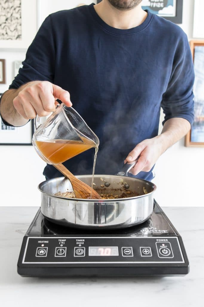Male in navy sweater pouring stock into a skillet on a portable stove