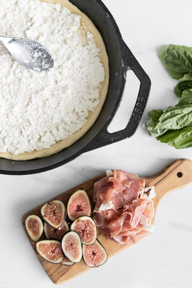 Cast iron pan with ricotta dressed pizza dough next to a small cutting board with figs and prosciutto