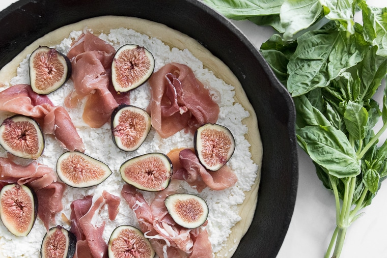 Close up of an uncooked pizza in a cast iron pan with ricotta cheese, prosciutto, and figs