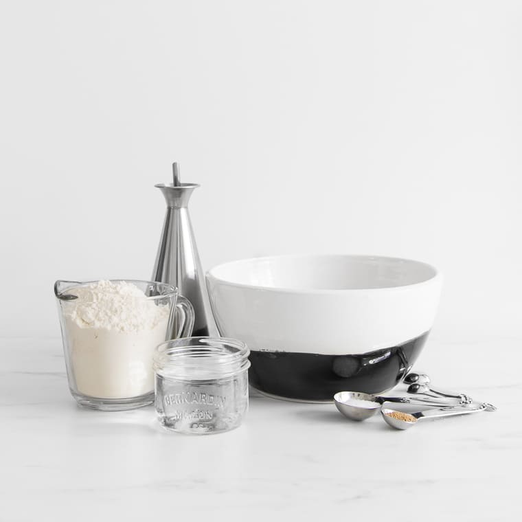 Black and white bowl, measuring cup with flour, olive oil tin, measuring spoons with yeast and salt for prosciutto pizza