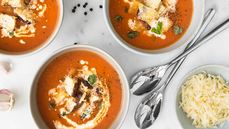 Close up of three bowls of Roasted Tomato Soup with Grilled Cheese Croutons next to a small bowl of grated cheese and spoons