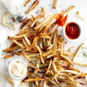 Crispy Oven Baked French Fries on marble with ketchup, mayo and salt