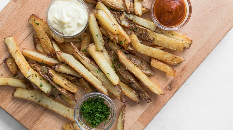 Close up of oven baked fries on wooden board with ketchup, mayo, chives