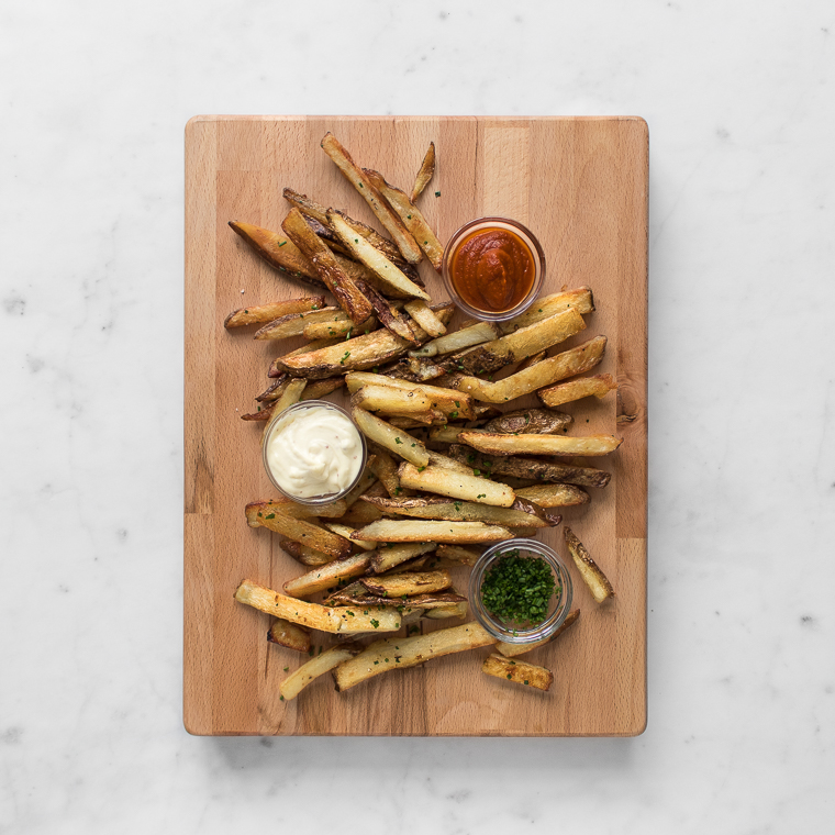Cooked fries on a cutting board