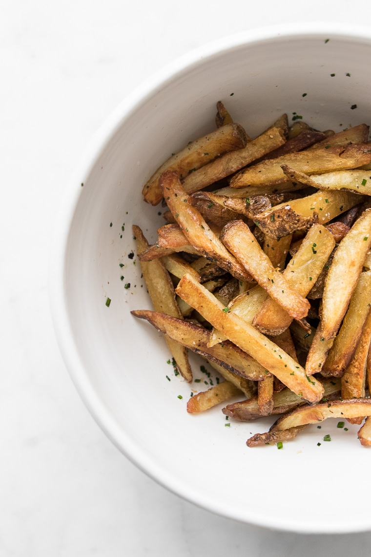 Seasoned oven baked fries in a white bowl