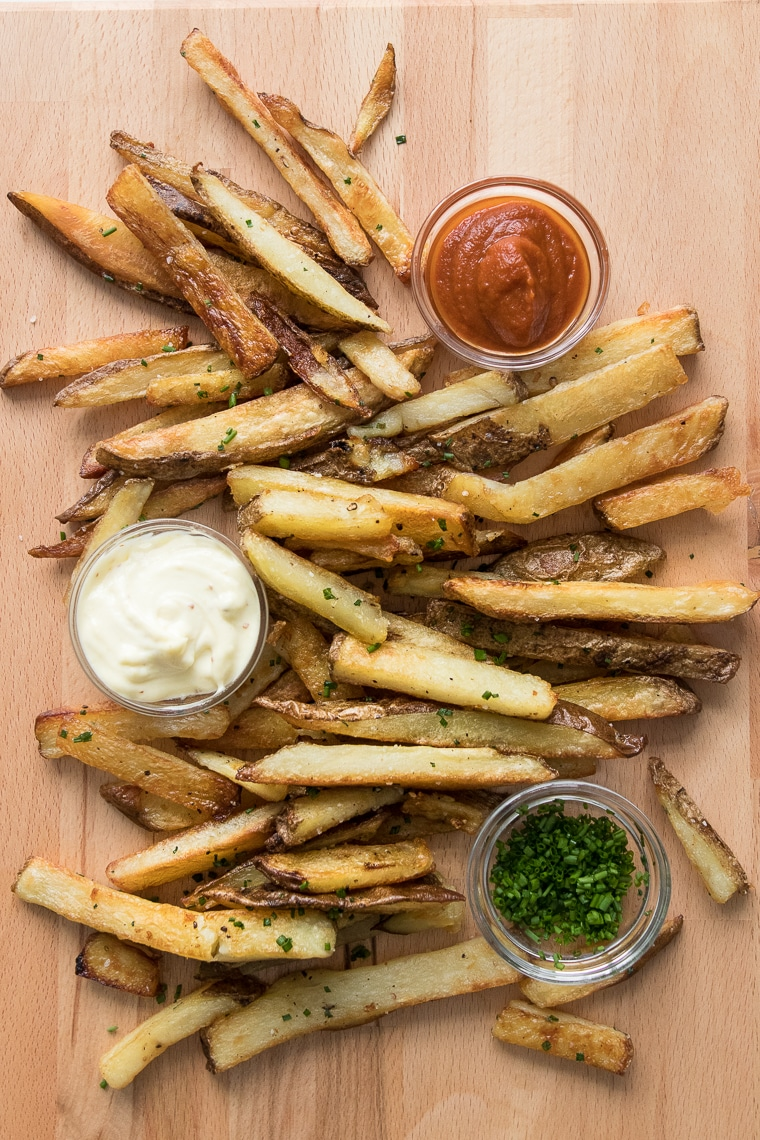 Oven baked fries on wooden cutting board