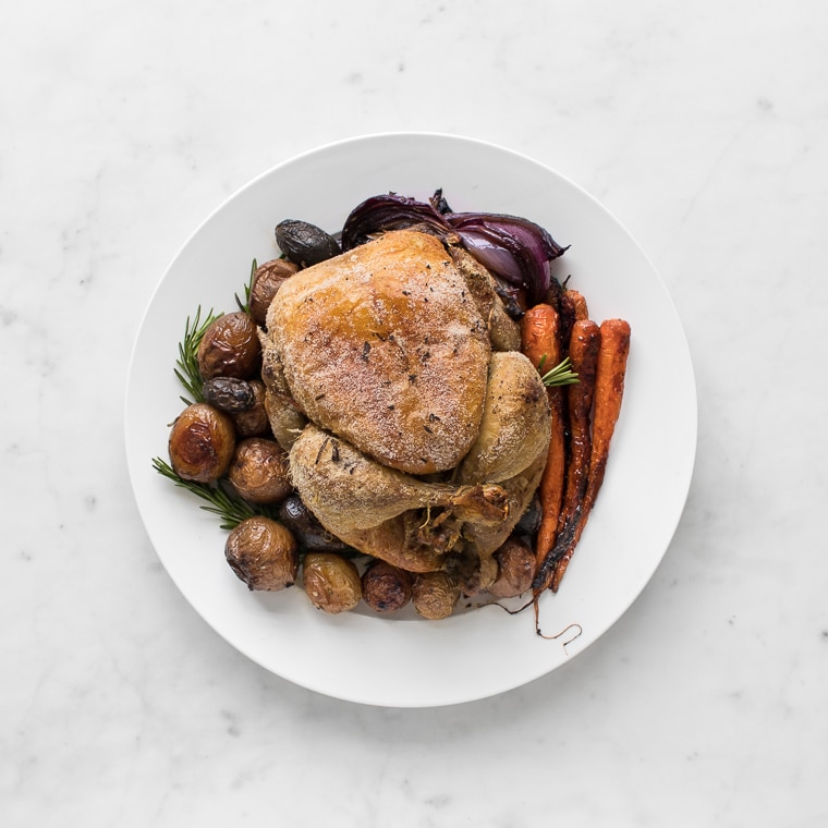 Whole Roast Chicken with Roasted Potatoes, Onions, and Carrots on a Large Round Plate with