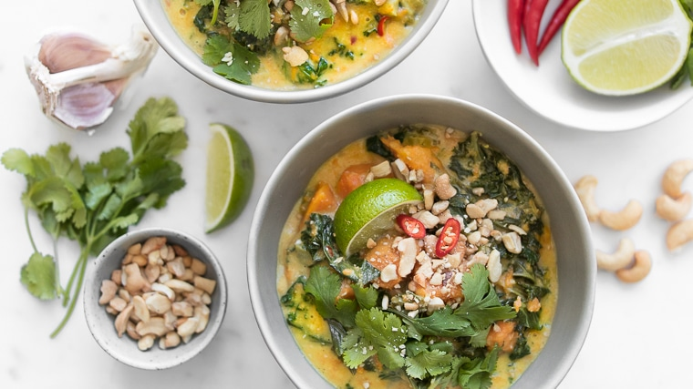 Close up of bowl of sweet potato stew garnished with cashews, cilantro and lime