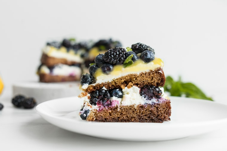 Slice of almond cake with lemon curd, berries, and ricotta