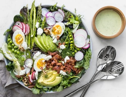 Green Spring Salad on a plate next to a bowl of Green Goddess Salad Dressing