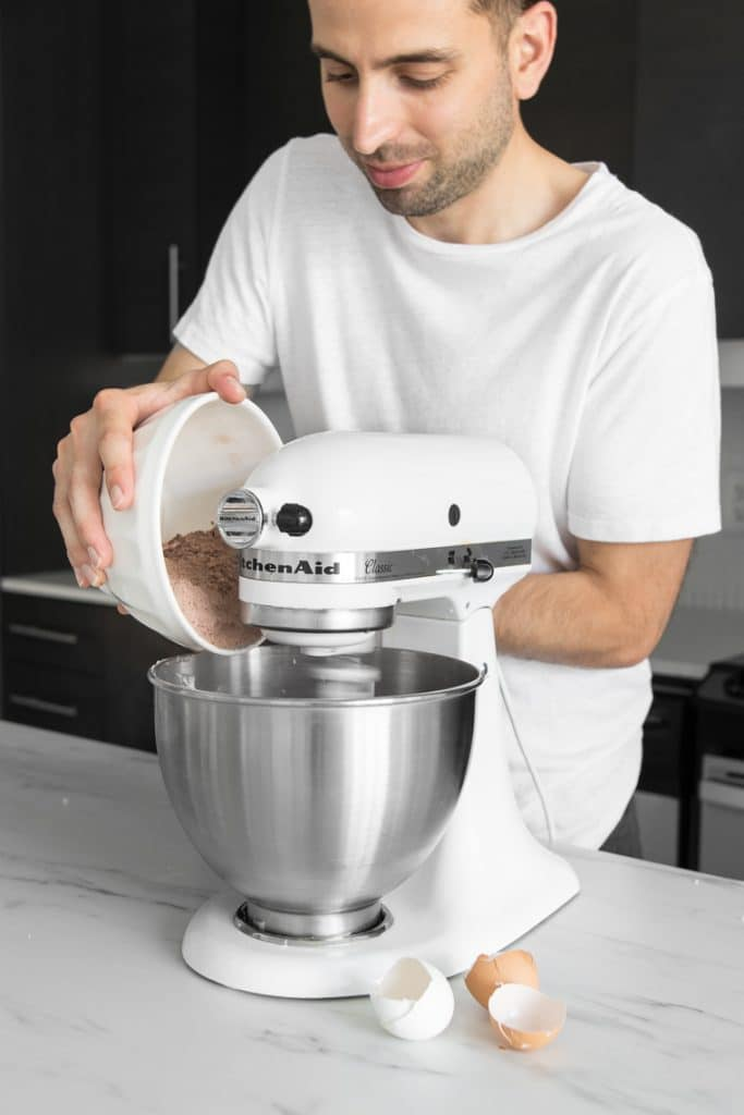 Guy in white shirt adding dry ingredients to Kitchen-Aid stand mixer