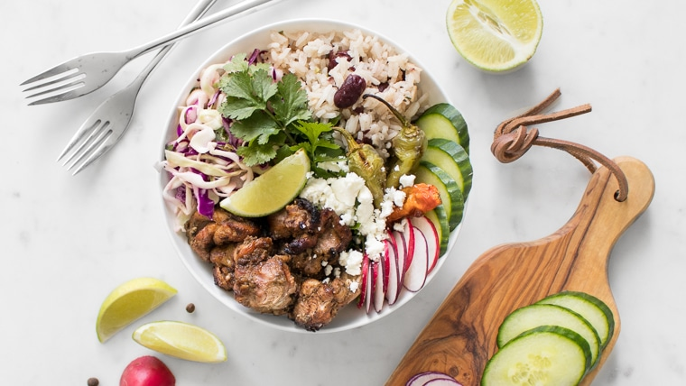 BBQ Jerk Chicken Bowl with Rice and Peas styled with lime, cucumbers and radishes