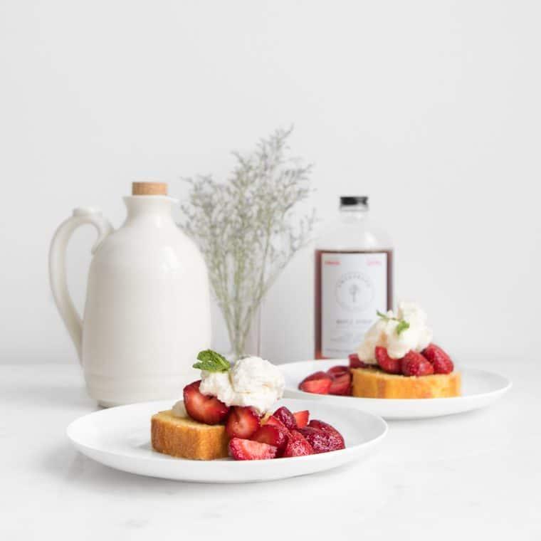 Strawberry shortcake cake with maple syrup bottles
