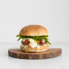 Pork burger topped with tomato sauce, mozzarella cheese, and lettuce