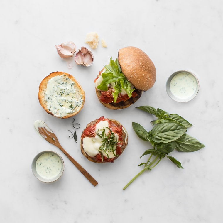 Flat lay of two pork parmigiana burgers with basil mayo