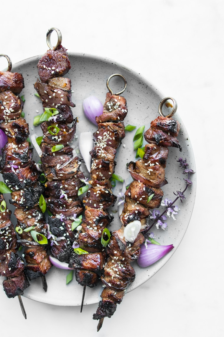 Close up of Sweet and Sour BBQ Beef Kebabs garnished with Green Onions and Sesame Seeds