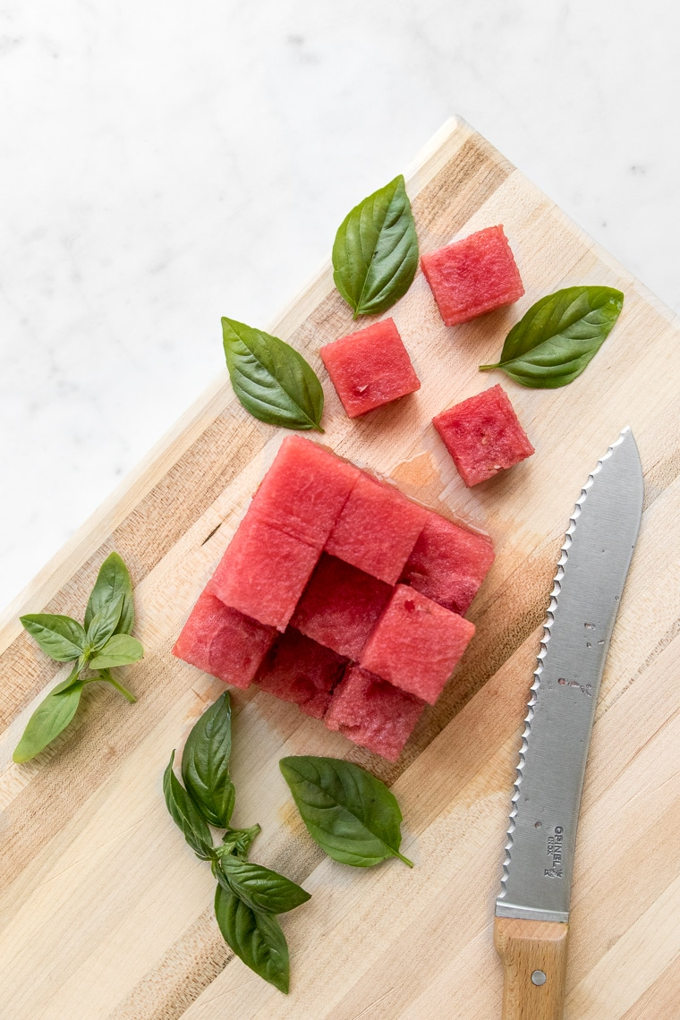 Watermelon cubes and basil leaves on a wooden cutting board