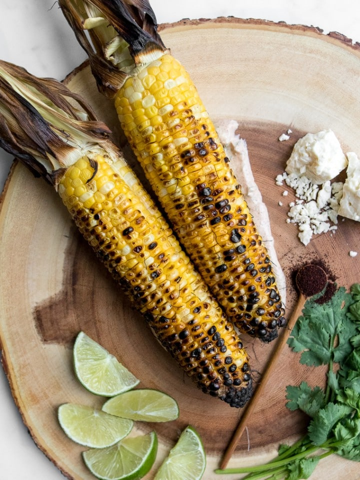 Two grilled corn cobs on a wooden board with lime wedges, cheese, and cilantro